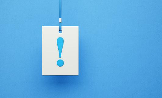 Biała kartka z niebieskim wykrzyknikiem zawieszona na niebieskim sznurku. Z tyłu niebieskie tło. Wyróżnienie ważnej informacji.