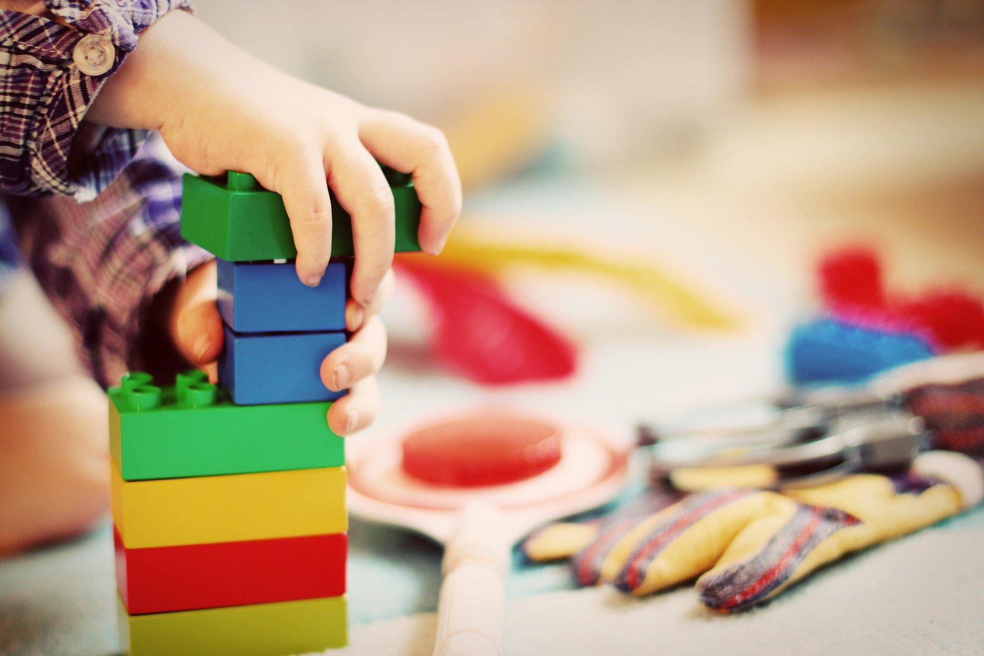 Na zdjeciu widać ręce dziecka układające wieżę z klocków, tło rozmazane z różnymi kolorowymi zabawkami.
