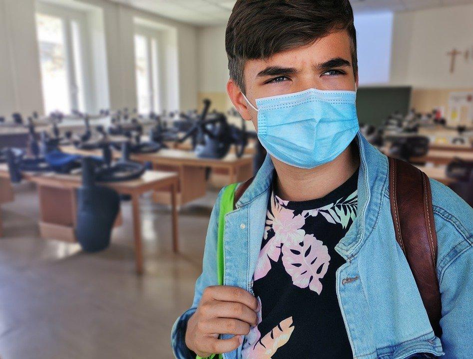 Chłopiec w maseczce stoi w sali lekcyjnej w szkole